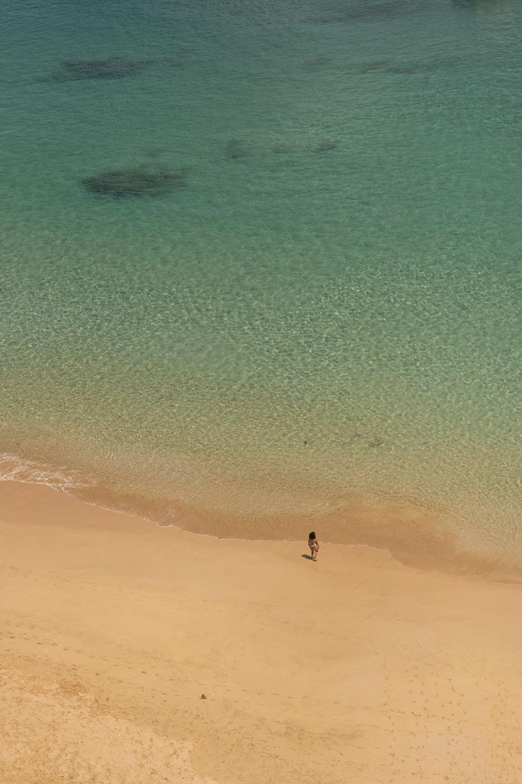 Praia do Sancho vista de cima, com uma única pessoa na areia e água azul clara