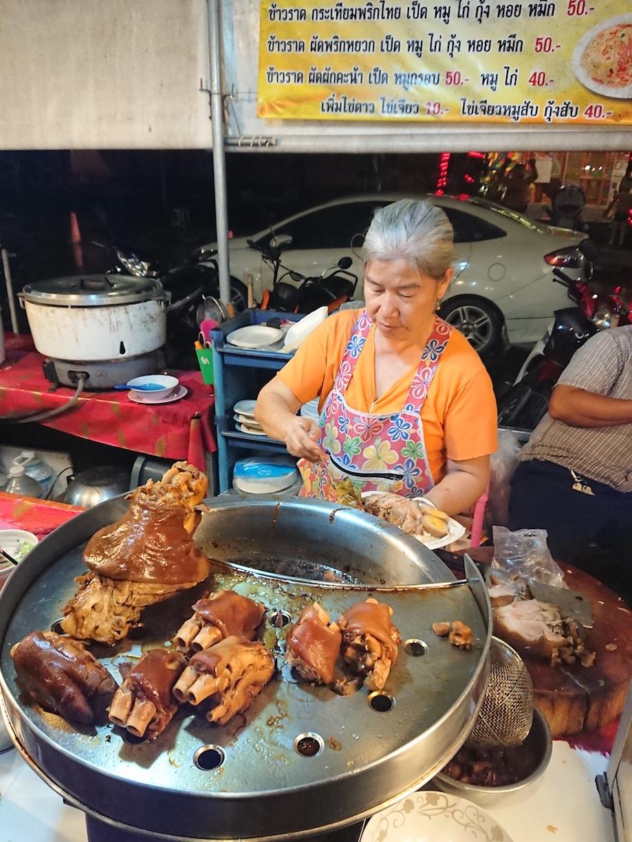 Senhora vende comida no mercado noturno de Trang, na Tailândia