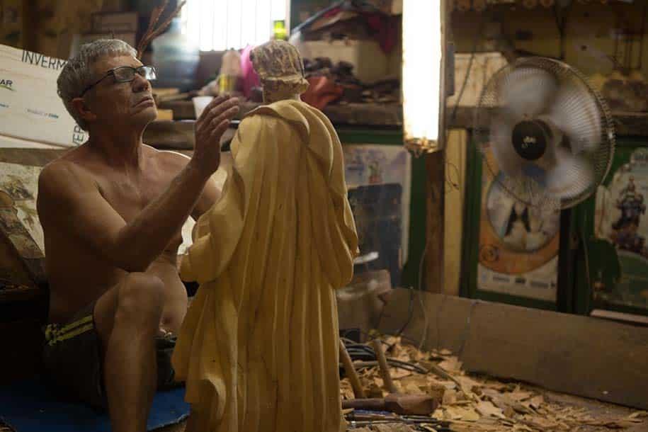 Artesão trabalha em santo de madeira na oficina do artesão mestre quincas