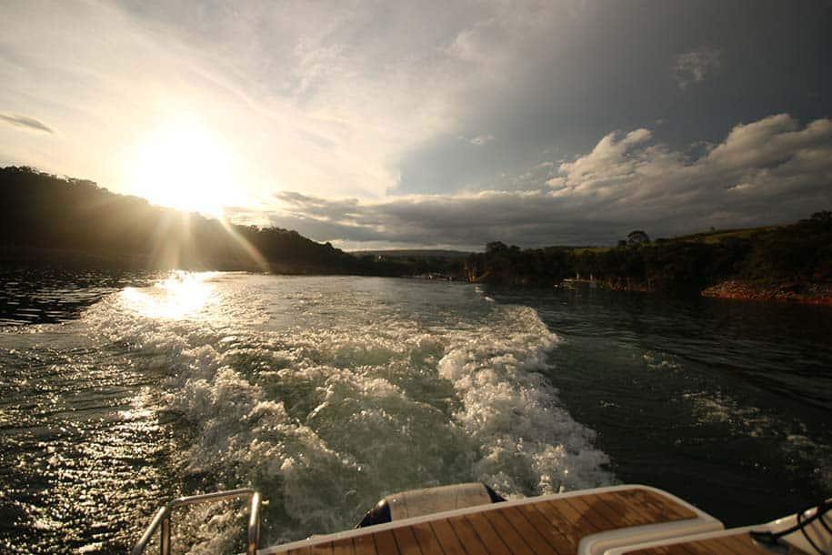 barco navega pelo Lago de Furnas ao pôr do sol