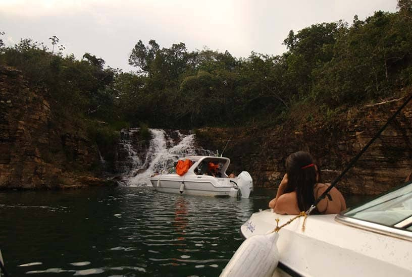 mulher observa cachoeira a partir de barco