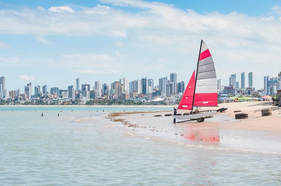 praia de João Pessoa, com cidade ao fundo e barco vermelho na areia