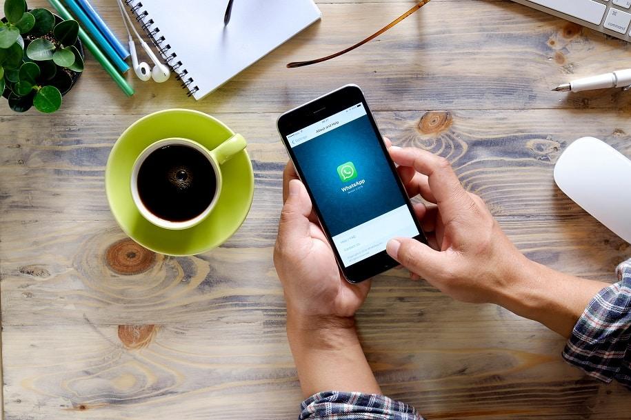 alguem ao telefone com o aplicativo whatsapp, uma xícara de café e uma mesa de escritório