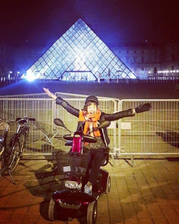 cadeirante em frente ao museu de louvre à noite