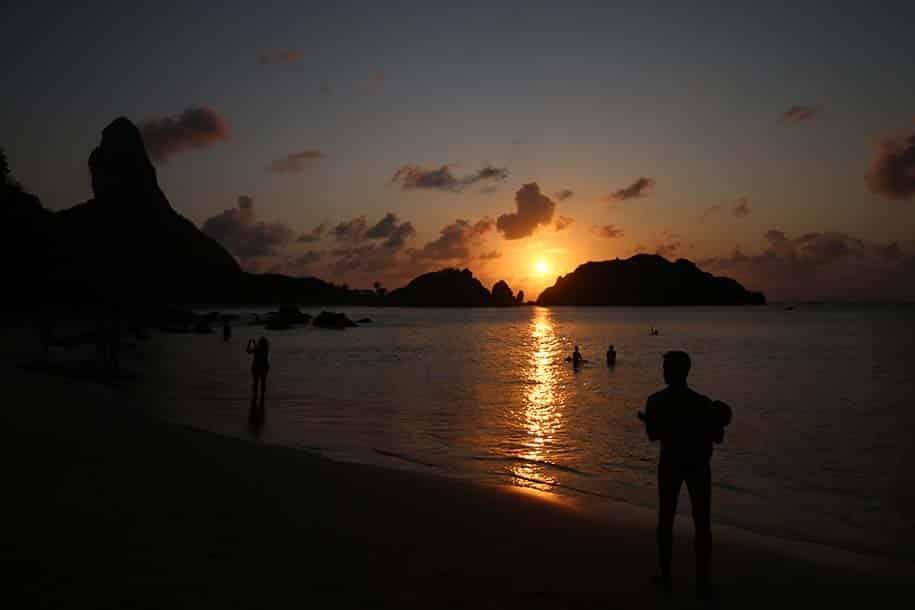 Pôr do sol na Praia do Cachorro, homem carrega bebê