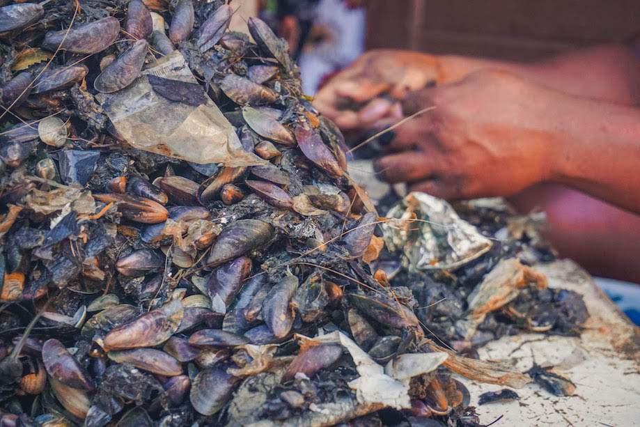 Mulher preparando o sururu pescado na Ilha de Deus
