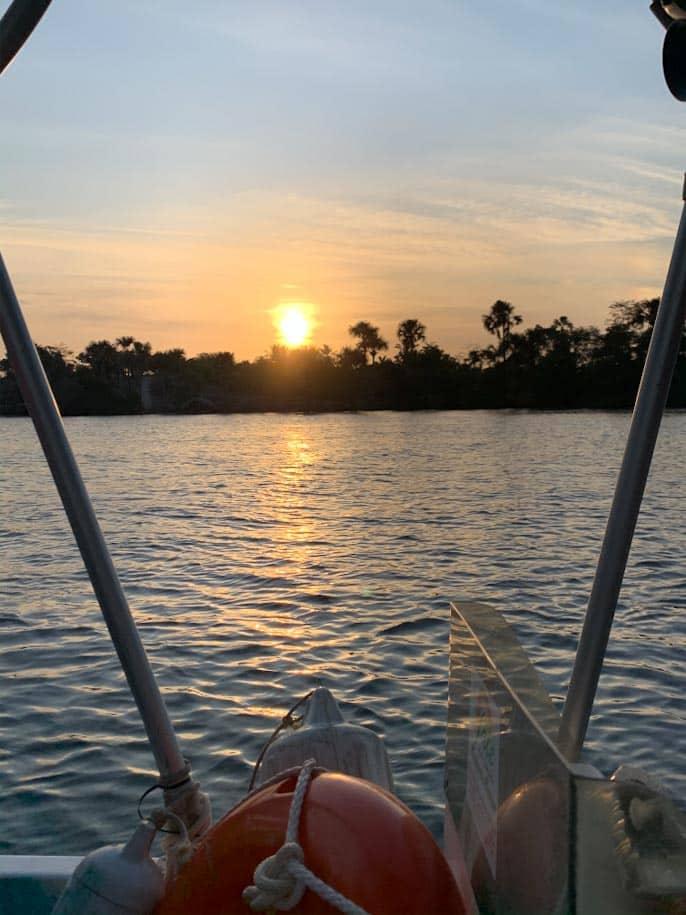 por do sol no rio preguiças em barreirinhas com árvores e barco