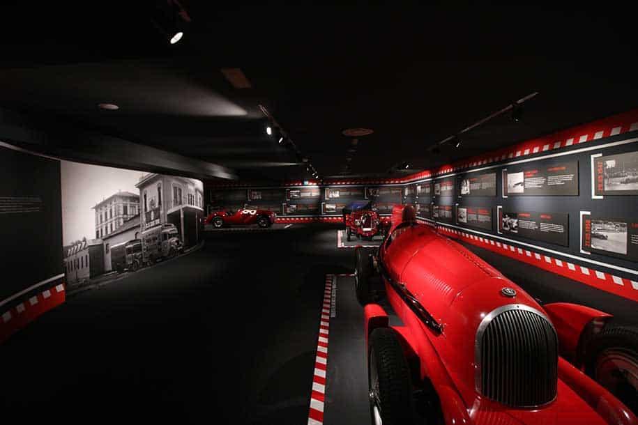 Três carros de corrida antigos, vermelhos, no museu da ferrari