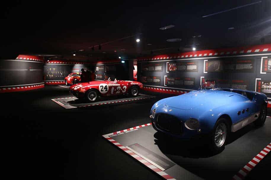 carro de corrida azul e duas ferraris vermelhas