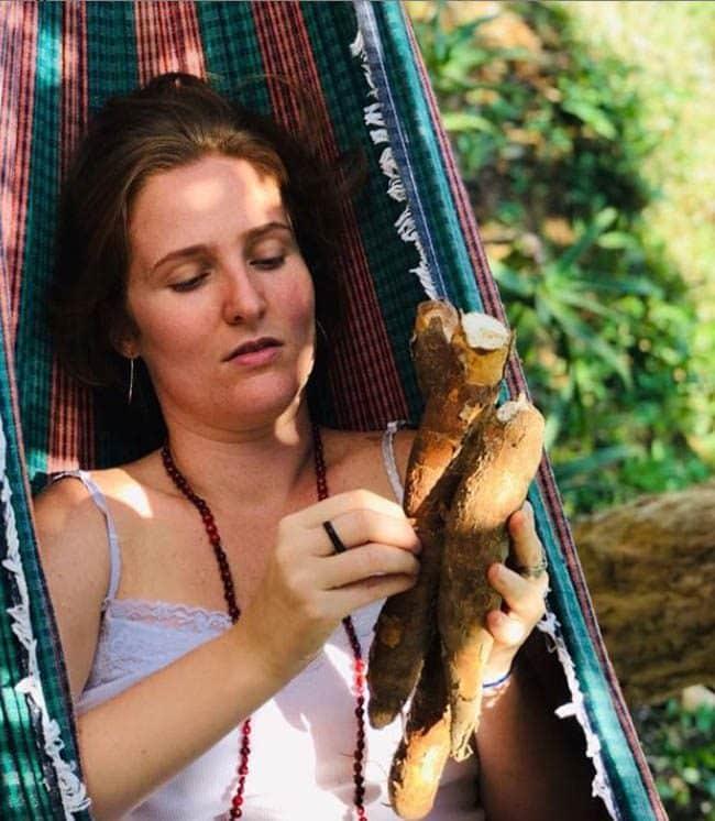 deitada na rede, segurando uma mandioca