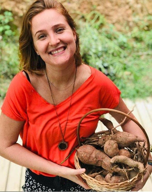 juliana carregando uma cesta de mandioca, alimento orgânico