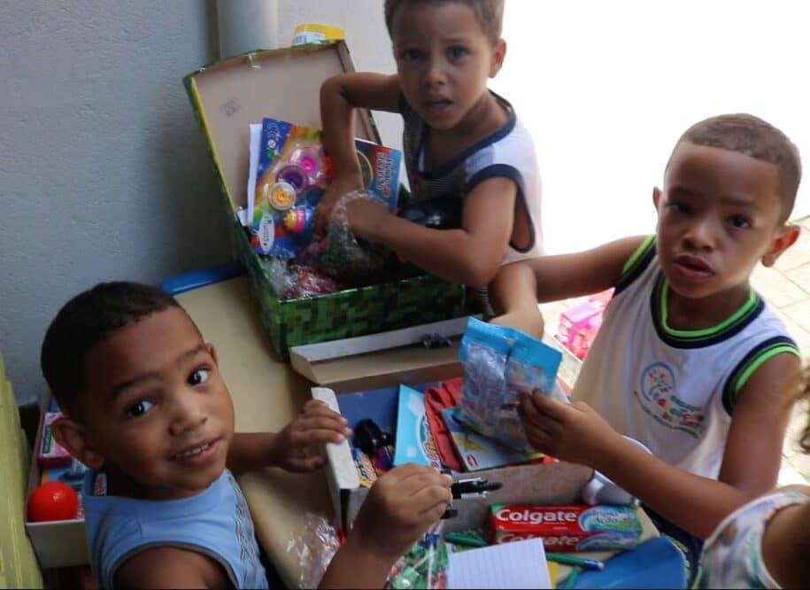 crianças abrindo presentes natal caixa de sapatos