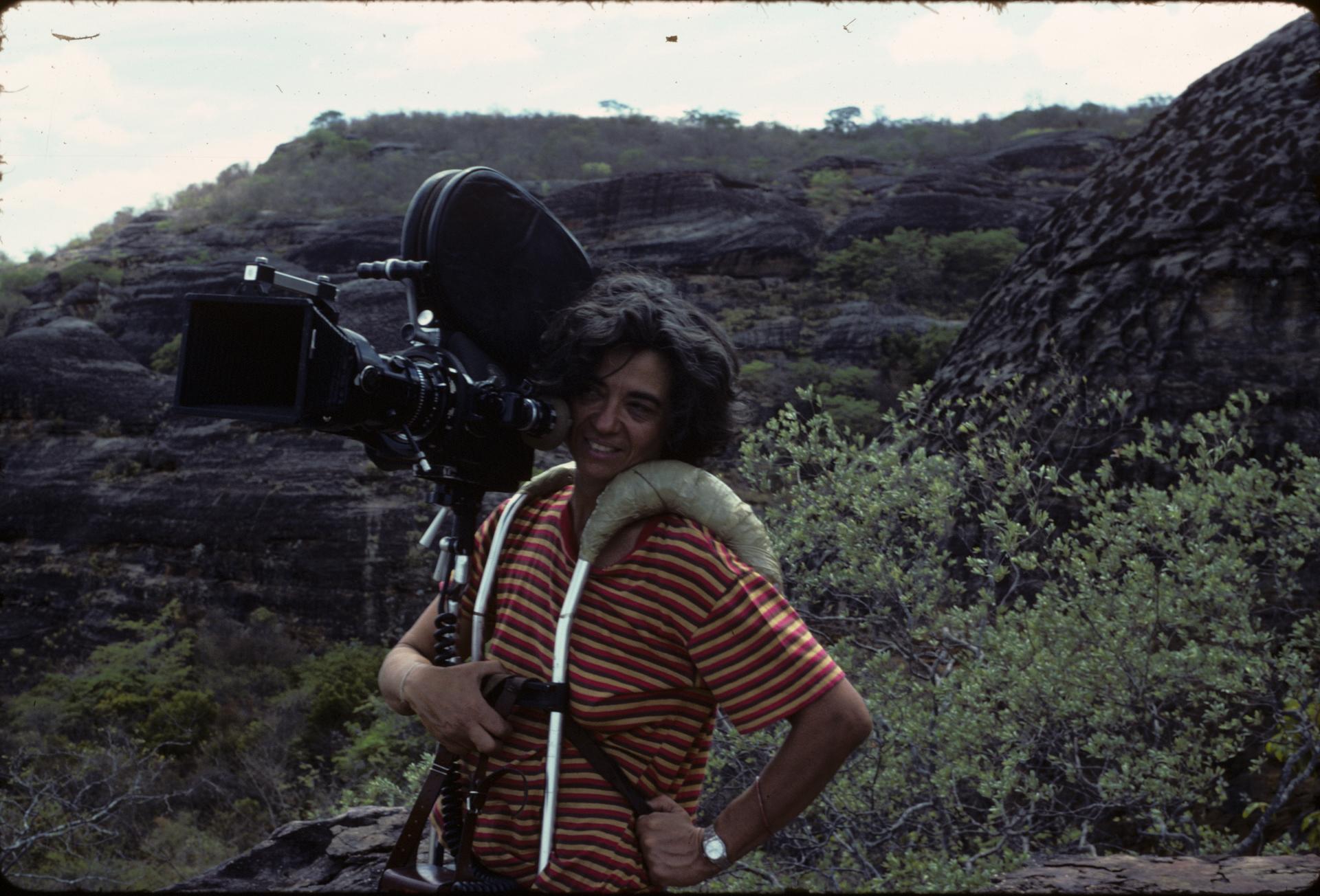 arqueóloga em campo escavando com uma câmera na mão